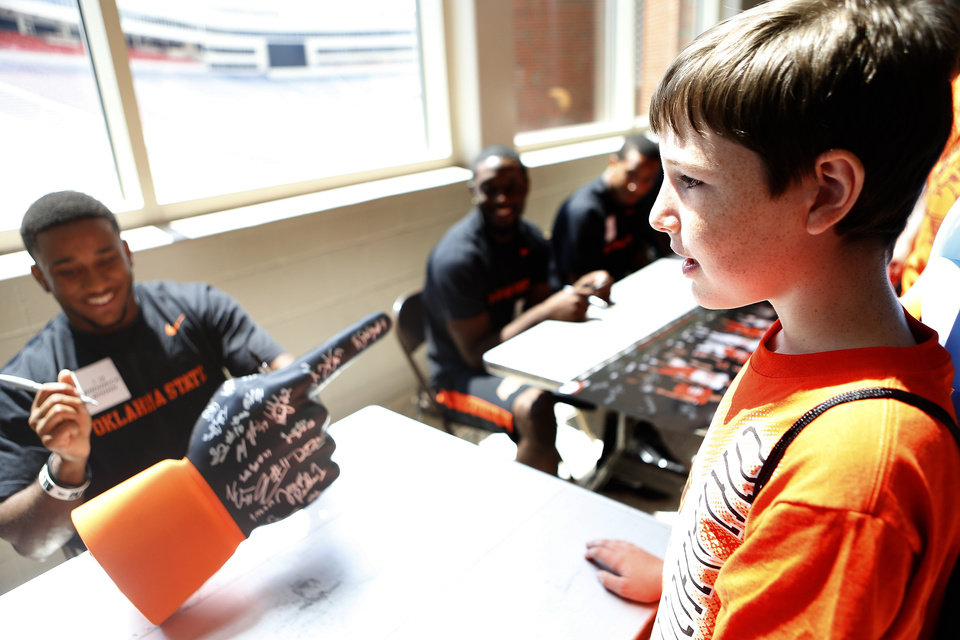 Photo - Oklahoma State football player Brodrick Brown signs an autograph for Montgomery Malome, 12, during Oklahoma State's Fan Appreciation Day at Gallagher-Iba Arena in Stillwater, Okla., Saturday, Aug. 4, 2012. Photo by Sarah Phipps, The Oklahoman
