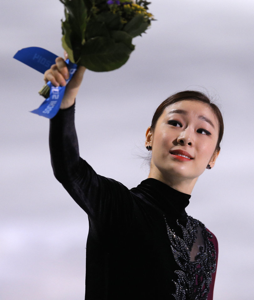 Photo - Yuna Kim of South Korea celebrates her second place as she stands on the podium following the women's free skate figure skating finals at the Iceberg Skating Palace during the 2014 Winter Olympics, Thursday, Feb. 20, 2014, in Sochi, Russia. (AP Photo/Vadim Ghirda)