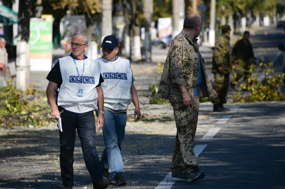 Photo - Members of the OSCE examine the scene of a shelling in the town of Donetsk, eastern Ukraine, Wednesday, Aug. 27, 2014. The Obama administration accused Russia on Wednesday of orchestrating a new military campaign in Ukraine, helping rebel forces expand their fight in the country's east and sending tanks, rocket launchers and armored vehicles toward communities elsewhere. (AP Photo/Mstislav Chernov)