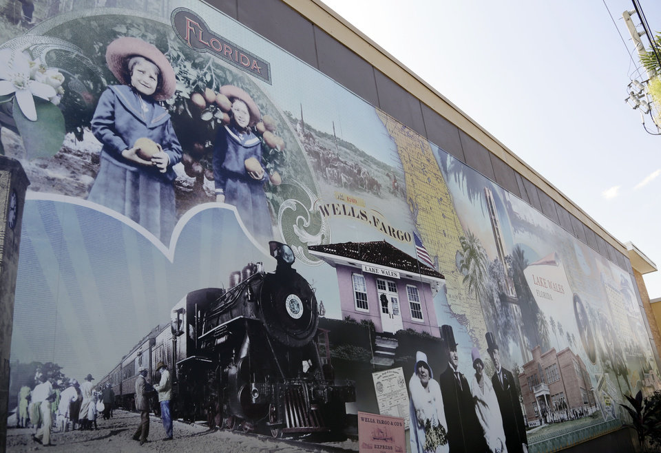 Photo - In this Wednesday, July 30, 2014 photo, a mural shows Marie and Hazel Kirch holding oranges in 1914, and the Orange Blossom Special train which brought passengers to Lake Wales in the 1920's, in downtown Lake Wales, Fla. Oranges and grapefruits have been farmed commercially in Florida since the 1800's. Florida's $9 billion citrus industry is facing its biggest threat yet by a tiny invasive bug called the Asian Citrus Psyllid, which carries bacteria that are left behind when the psyllid feeds on a citrus tree's leaves. (AP Photo/Lynne Sladky)