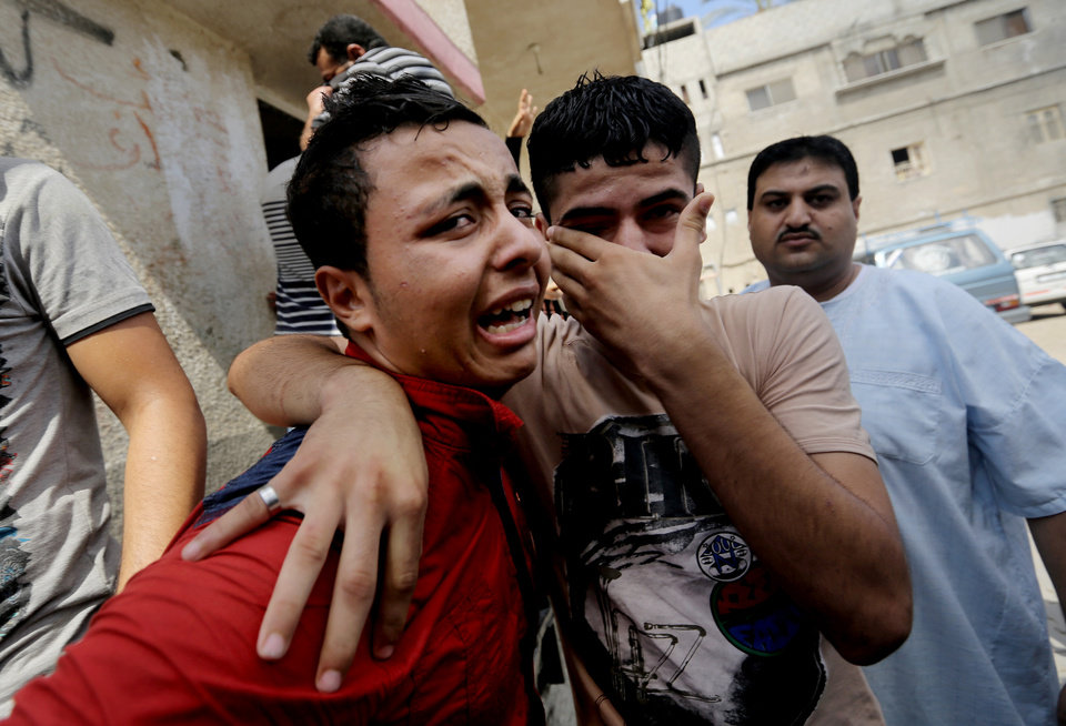 Photo - Palestinian relatives mourn for Qasim Alwan, 4, and Imad Alwan, 6, who were killed Friday by an Israeli tank shell, during their funeral in Gaza City, Saturday, July 19, 2014. Relatives say the tank shell kit the Alwan family's kitchen, killing Qasim and Imad. Rizk Hayek, 1, who lived nearby, was killed by shrapnel. (AP Photo/Hatem Moussa)