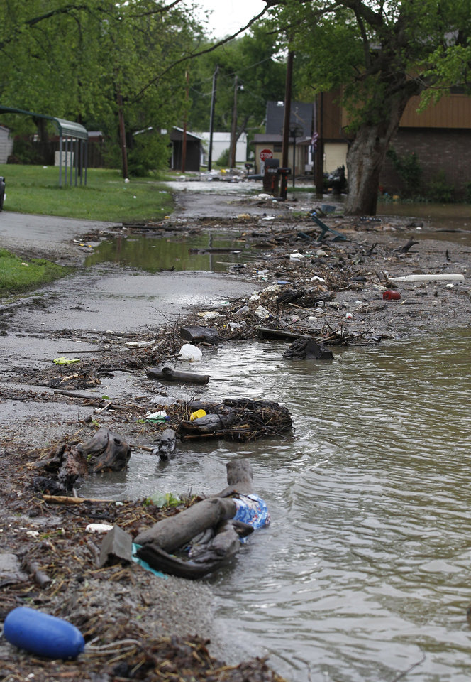 Photo - Debris and floodwaters from the Ohio River fill the streets in Utica, Ind., Wednesday, April 27, 2011. (AP Photo/Darron Cummings)