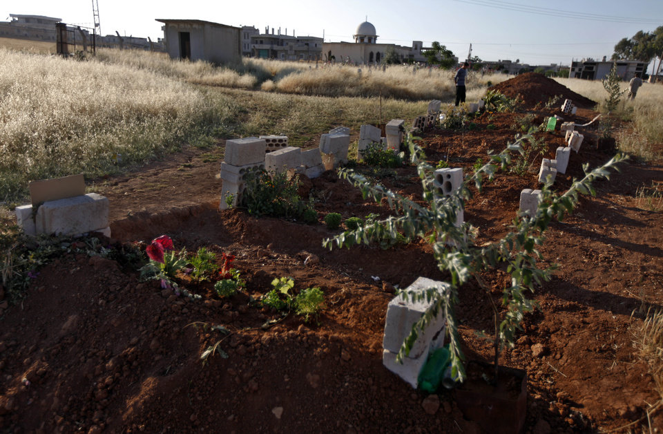 Photo -   In a Tuesday, June 5, 2012 photo, a Syrian man stands next to a grave of 40 Syrians were killed in a military raid by the Syrian army in April 2012, in the town of Taftanaz,15 kilometers east of Idlib, Syria. At dawn on April 3, Syrian forces shelled the town in the first volley of what residents say was a massive assault after a string of large protests calling for the end of the autocratic rule of President Bashar Assad. (AP Photo/Khalil Hamra)