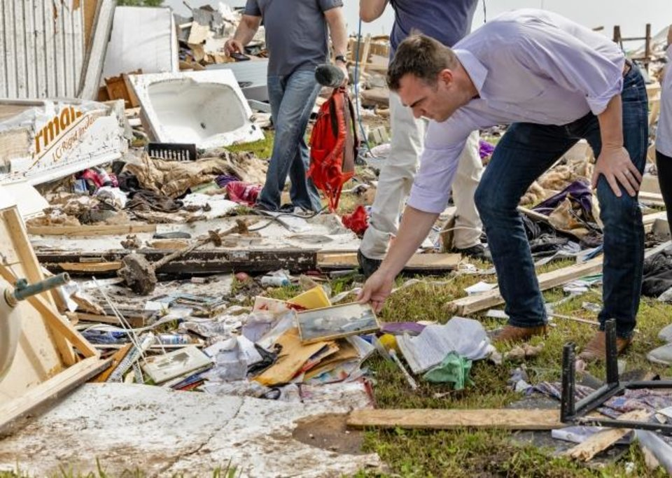 Photo -  Gov. Kevin Stitt picks up a photo out of the debris as he tours the aftermath of a tornado in El Reno, Okla. on Monday, May 27, 2019. The EF3 tornado hit the American Budget Value Inn and Skyview Mobile Home Park on Saturday night killing two people and injuring many others. (Chris Landsberger/The Oklahoman via AP)