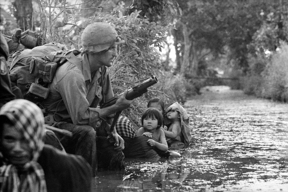 Photo -   FILE - In this Jan. 1, 1966 file photo, two South Vietnamese children gaze at an American paratrooper holding an M79 grenade launcher as they cling to their mothers who huddle against a canal bank for protection from Viet Cong sniper fire in the Bao Trai area, 20 miles west of Saigon, Vietnam. Faas, a prize-winning combat photographer who carved out new standards for covering war with a camera and became one of the world's legendary photojournalists in nearly half a century with The Associated Press, died Thursday May 10, 2012. He was 79. (AP Photo/Horst Faas)