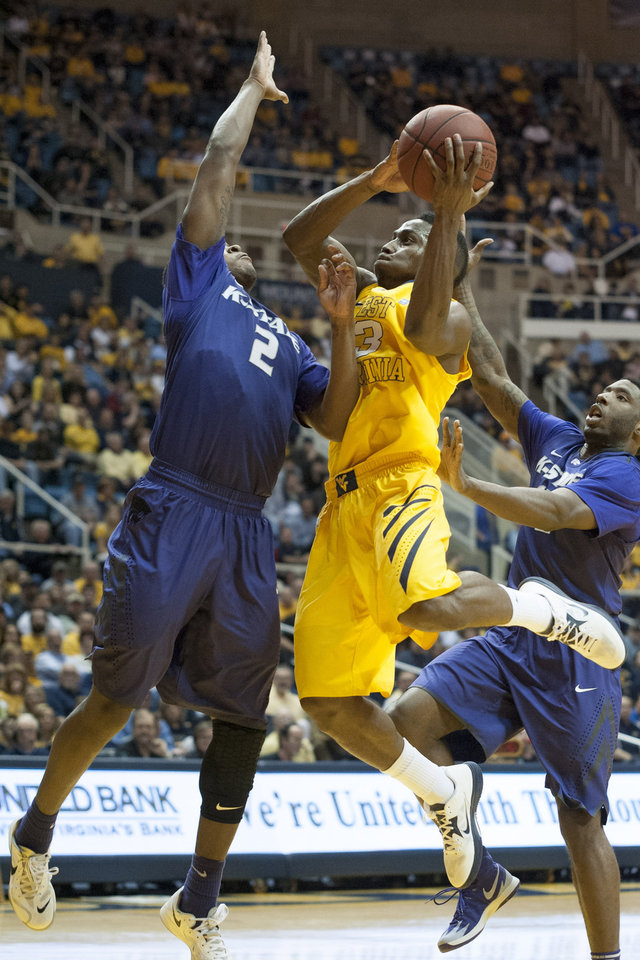 Photo - West Virginia's Juwan Staten, right, drives to the basket as Kansas State's Marcus Foster defends during the second half of an NCAA college basketball game Saturday, Feb. 1, 2014, in Morgantown, W.Va. West Virginia won 81-71. (AP Photo/Andrew Ferguson)