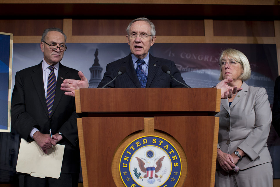 Photo - Senate Majority Leader Sen. Harry Reid, D-Nev., center, gestures during a news conference with Sen. Chuck Schumer, D-N.Y., left, Sen. Dick Durbin, D-Ill. (not shown) and Sen. Patty Muray, D-Was., right, during on Capitol Hill on Saturday, Oct. 12, 2013 in Washington. The federal government remains partially shut down and faces a first-ever default between Oct. 17 and the end of the month. (AP Photo/ Evan Vucci)  ORG XMIT: DCEV121