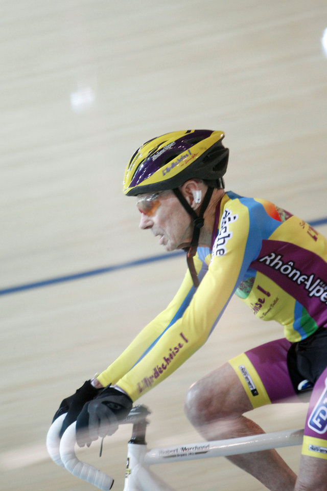 Photo - French cyclist Robert Marchand, aged 102, cycles in a bid to beat his record for distance cycled in one hour, at the velodrome of Saint-Quentin en Yvelines, outside Paris, Friday, Jan. 31, 2014. The 102-year-old broke his own world record in the over-100s category Friday, riding 26.927 kilometers (16.7 miles) in one hour, more than 2.5 kilometers better than his previous best time in the race against the clock two years ago. (AP Photo/Thibault Camus)