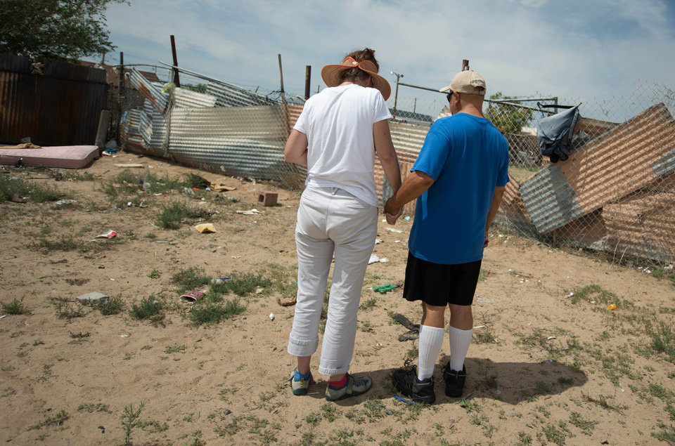 Photo - Concerned citizens observe a moment of silence, Monday, July 21, 2014 in the field where two homeless men were bludgeoned to death by teenagers over the weekend near in Albuquerque, N.M. (AP Photo/Albuquerque Journal, Roberto E. Rosales)