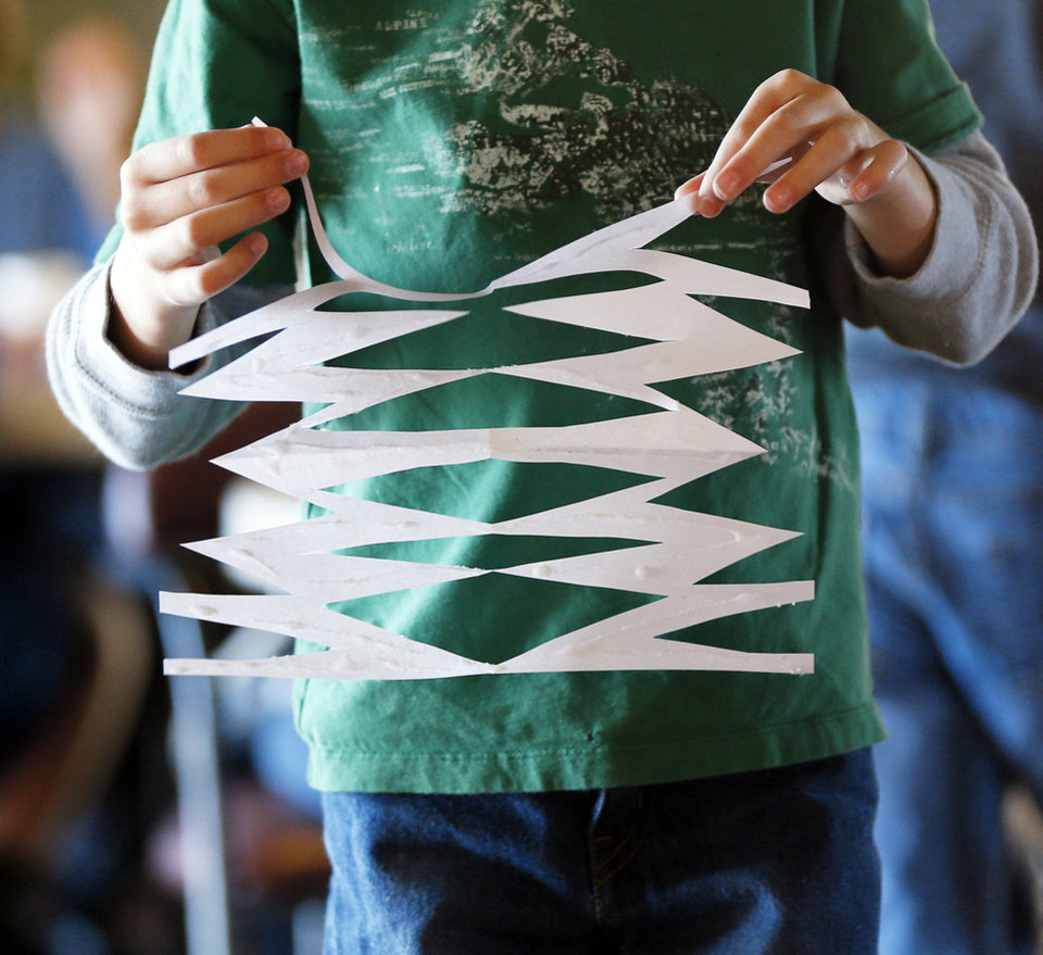 Photo - Peyton Murray, 7, carries a paper snowflake he made at New Life Bible Church in Norman, Okla., Saturday, Dec. 29, 2012. New Life Bible Church, as well as several schools in Norman, are making snowflakes to send to Newtown, Conn., to greet children in their new school building. Photo by Nate Billings, The Oklahoman