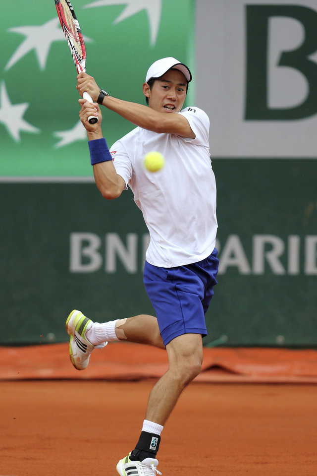 Photo - Japan's Kei Nishikori returns the ball during the first round match of the French Open tennis tournament against Slovakia's Martin Klizan at the Roland Garros stadium, in Paris, France, Monday, May 26, 2014. (AP Photo/David Vincent)