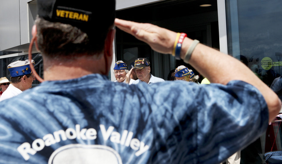 Photo - Ken Wood, 64, a Vietnam Veteran from Roanoke salutes World War II veterans as they arrive at Roanoke-Blacksburg Regional Airport  in Roanoke, Va., Friday, June 5, 2014, after arriving from Palm Beach International Airport, courtesy of Honor Flight Network. The veterans were arriving for the 70th Anniversary of the Invasion of Normandy, at the National D-Day Memorial in Bedford, about 40 minutes east of Roanoke. (AP Photo/The Roanoke Times, Stephanie Klein-Davis)  LOCAL TV OUT; SALEM TIMES REGISTER OUT; FINCASTLE HERALD OUT;  CHRISTIANBURG NEWS MESSENGER OUT; RADFORD NEWS JOURNAL OUT; ROANOKE STAR SENTINEL OUT