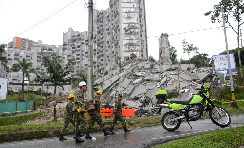Photo - Soldiers walk past the remains of a 22-story building that imploded, in Medellin, Colombia, Monday, Oct. 14, 2013. Heavy rains and fears an adjacent building could fall have forced a halt in the search for 11 people trapped in the ruins of a collapsed Colombian apartment tower. The city's emergency management director says he hasn't lost hope that someone has survived in the 22-story building that imploded on Saturday night, but that the odds are against it, given the weight of the rubble. (AP Photo /Luis Benavides)