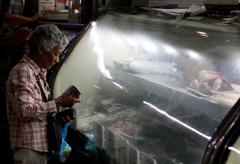 In this April 6, 2013 photo, a customer looks at fresh fish for sale at a market in Caracas, Venezuela. The country of 30 million people imports nearly 70 percent of its food, including products it did not need to before Hugo Chavez became president, including beef, coffee and rice. (AP Photo/Fernando Llano)