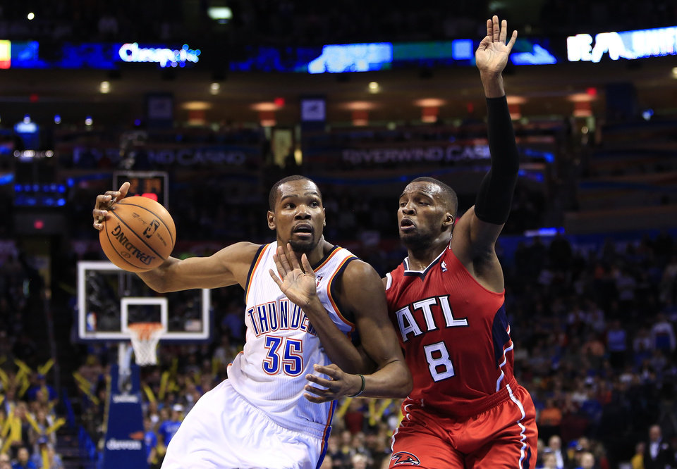 Photo - Oklahoma City Thunder forward Kevin Durant (35) drives to the basket as Atlanta Hawks guard Shelvin Mack (8) defends during the fourth quarter of an NBA basketball game, Monday, Jan. 27, 2014, in Oklahoma City. Oklahoma City won 111-109. (AP Photo/Alonzo Adams)