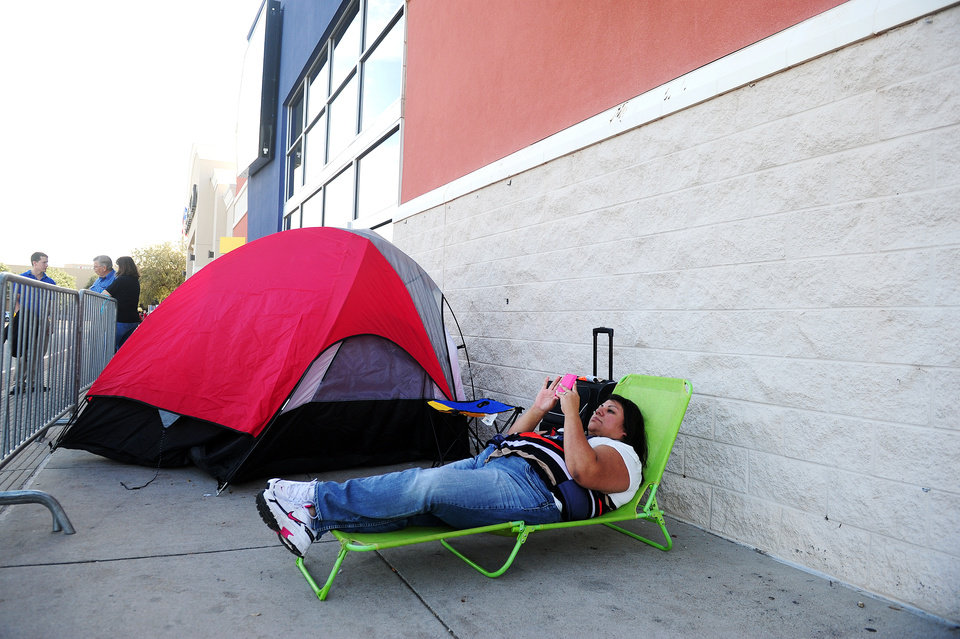 Photo -   Susan Ellis reclines on her lawn chair as she holds her place as number two in line for Black Friday deals on Wednesday, Nov. 21, 2012 at Best Buy in Abilene, Texas. Ellis said she plans to wait outside the store until the doors open at midnight on Thursday, Nov. 22, 2012. Her husband will take her place in line long enough for Ellis to stop by her mother's home for a bite of Thanksgiving dinner. (AP Photo/Abilene Reporter-News, Joy Lewis)