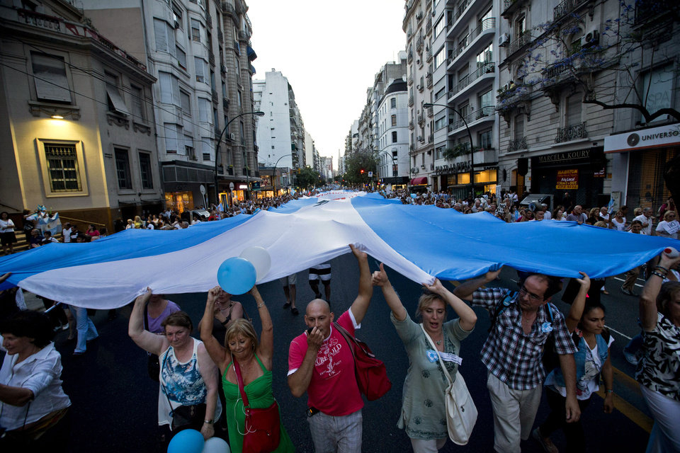 Photo -   Protesters carry a large Argentine flag during an anti-government demonstration in Buenos Aires, Argentina, Thursday, Nov. 8, 2012. Thousands of people marched against rising inflation, crime, exchange controls and to express their fear to a constitutional reform that could open the way for a third consecutive reelection of Argentina's President Cristina Fernandez. (AP Photo/Victor R. Caivano)