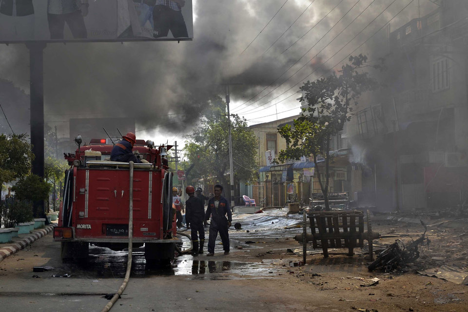 Myanmar firefighters battle fires in burning buildings following ethnic unrest between Buddhists and Muslims in Meikhtila, Mandalay division, about 550 kilometers (340 miles) north of Yangon, Myanmar, Friday, March 22, 2013. Black smoke and flames poured from the hulks of destroyed buildings in the central city of Meikhtila, where the unrest erupted Wednesday in the latest challenge to Myanmar\'s ever-precarious transition to democratic rule. (AP Photo/Khin Maung Win)