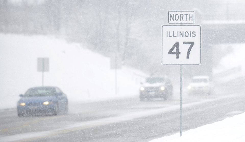 Photo - Visibility along Route 47 in the Chicago suburb of Lily Lake, Ill. is very limited as wet snow continues to fall during a snow storm on Tuesday, March 5, 2013. (AP Photo/Daily Herald, Laura Stoecker) MANDATORY CREDIT; MAGS OUT; TV OUT