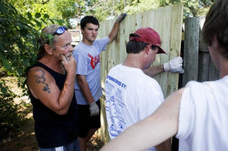Dale Osborne, left, inspects as Grant Matthis, center, and Tim Moran from the Catholic HEART Workcamp move a fence panel in Osborne's backyard in the Riverpark neighborhood in southwest Oklahoma City. <strong>ZACH GRAY - THE OKLAHOMAN</strong>