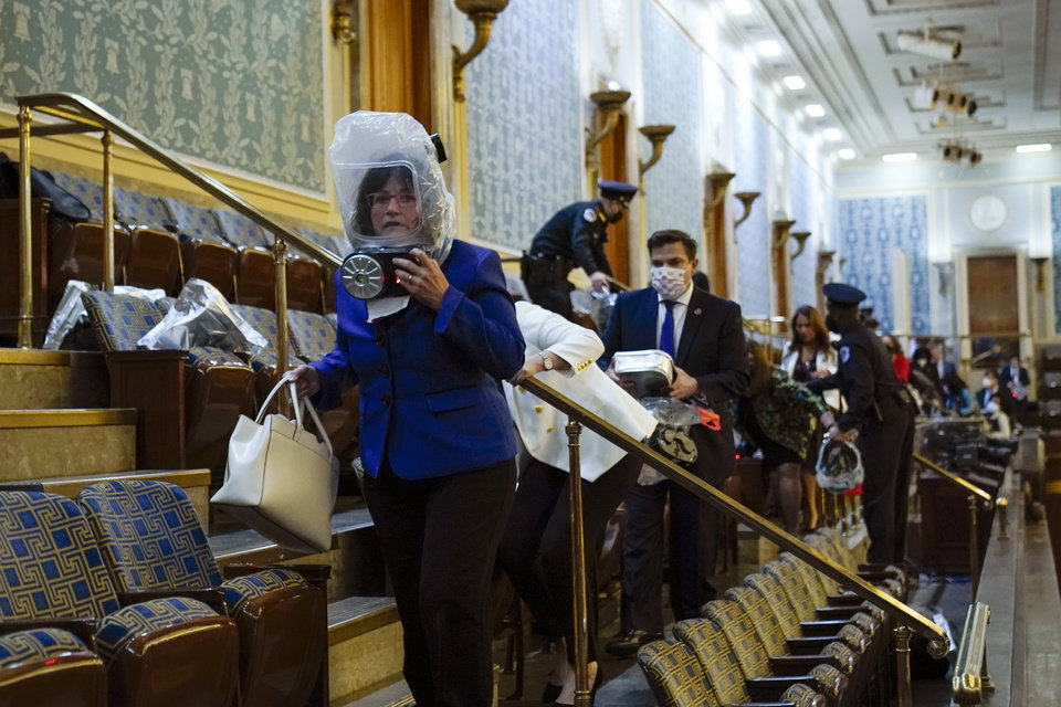 Photo - People shelter in the House gallery as protesters try to break into the House Chamber at the U.S. Capitol on Wednesday, Jan. 6, 2021, in Washington. (AP Photo/Andrew Harnik)