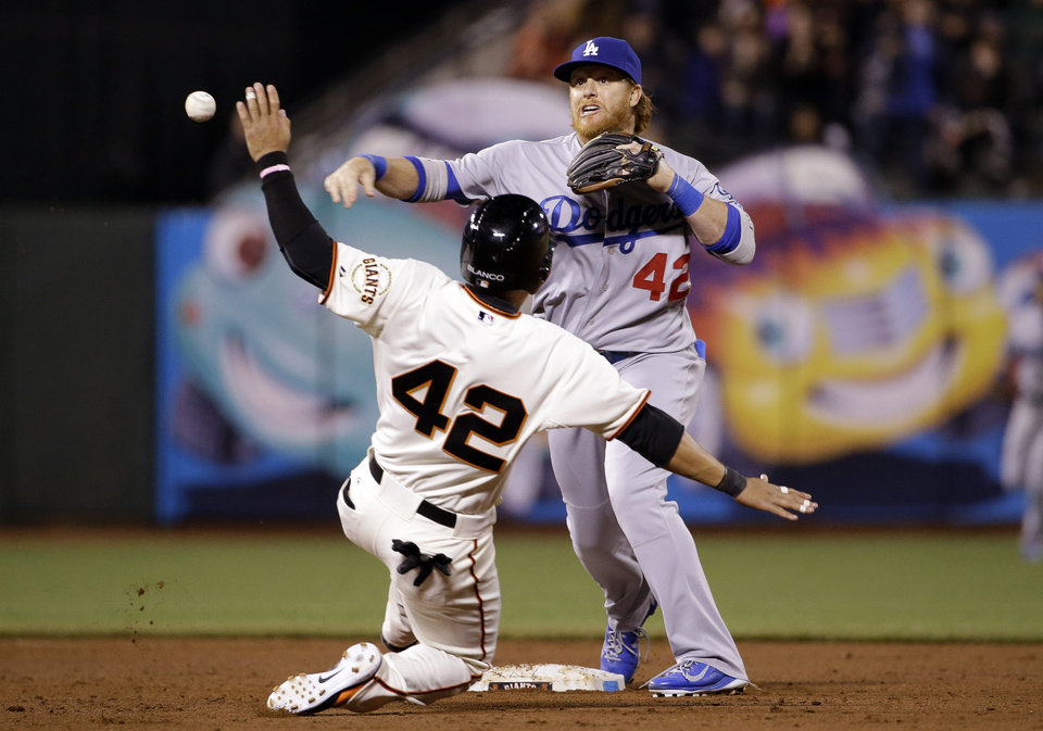 Photo - Los Angeles Dodgers second baseman Justin Turner, top, turns a double play over San Francisco Giants' Gregor Blanco after a ground ball by Brandon Hicks during the eighth inning of a baseball game on Tuesday, April 15, 2014, in San Francisco. (AP Photo/Marcio Jose Sanchez)