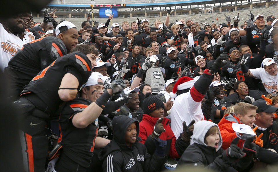 Photo - OSU celebrates their win following the Heart of Dallas Bowl football game between the Oklahoma State University (OSU) and Purdue University at the Cotton Bowl in Dallas,  Tuesday,Jan. 1, 2013. Photo by Sarah Phipps, The Oklahoman