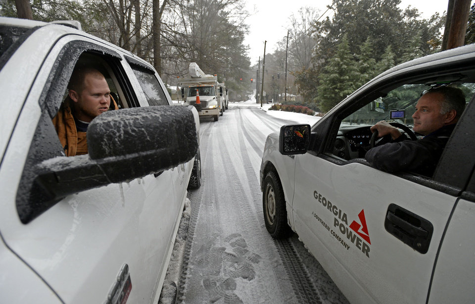 Photo - Power company crew members prepare to work on a downed power line that fell near Emory University after freezing rain, sleet and snow toppled trees and power lines during a winter storm on Wednesday, Feb. 12, 2014, in Atlanta. Over 175,000 residences and businesses statewide were without electricity. (AP Photo/David Tulis)