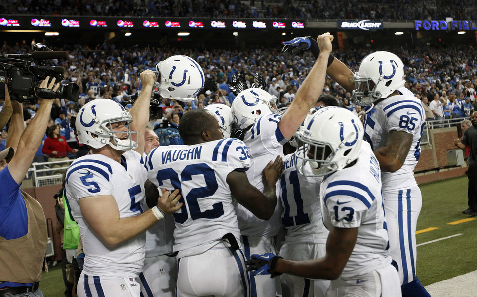 Photo - Indianapolis Colts quarterback Andrew Luck with teammates after a 14-yard touchdown to wide receiver Donnie Avery as time expired against the Detroit Lions in the fourth quarter of an NFL football game in Detroit, Sunday, Nov. 2, 2012. Indianapolis won 35-33. (AP Photo/Paul Sancya)