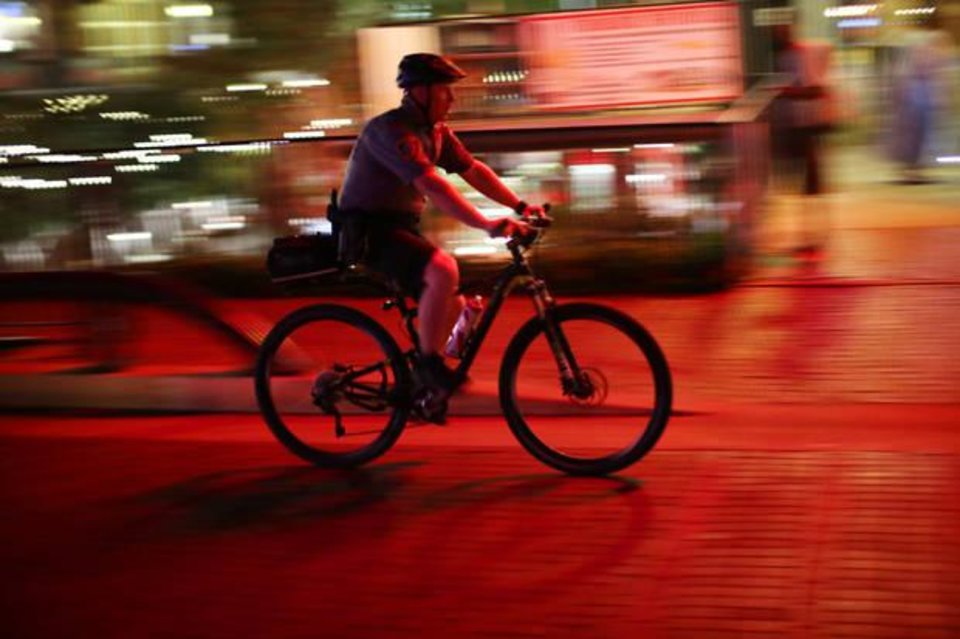 Photo -  An Oklahoma City bicycle officer rides along the S Oklahoma Avenue in Bricktown. [PHOTO BY DOUG HOKE, THE OKLAHOMAN]