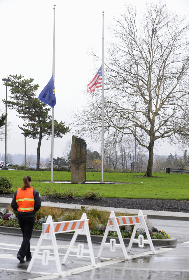 Photo - Flags fly at half staff Wednesday Dec. 12, 2012, at the entrance to the scene of a multiple shooting Tuesday at Clackamas Town Center Mall in Portland, Ore. Jacob Tyler Roberts  killed two people and himself in the shooting rampage. (AP Photo/Greg Wahl-Stephens)