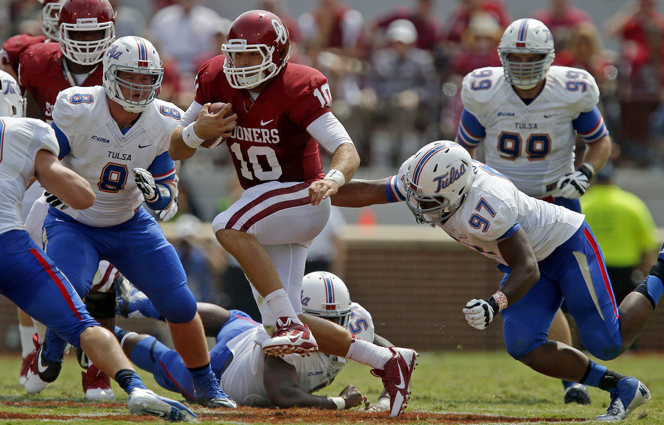 Photo - Oklahoma's Blake Bell (10) runs between Tulsa's Jesse Brubaker (8) and Brentom Todd (97) during a college football game between the University of Oklahoma Sooners (OU) and the Tulsa Golden Hurricane at Gaylord Family-Oklahoma Memorial Stadium in Norman, Okla., on Saturday, Sept. 14, 2013. Oklahoma won 51-20. Photo by Bryan Terry, The Oklahoman