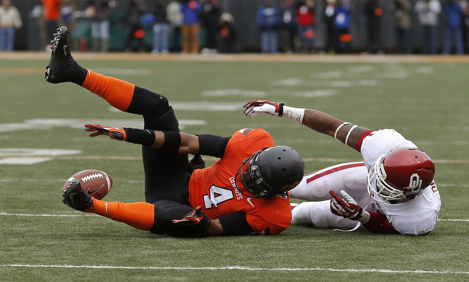Photo - Oklahoma State's Justin Gilbert (4) can't hold on for an interception beside Oklahoma's Lacoltan Bester (11) during Oklahoma's final drive in the Bedlam college football game between the Oklahoma State University Cowboys (OSU) and the University of Oklahoma Sooners (OU) at Boone Pickens Stadium in Stillwater, Okla., Saturday, Dec. 7, 2013. Oklahoma won 33-24. Photo by Bryan Terry, The Oklahoman
