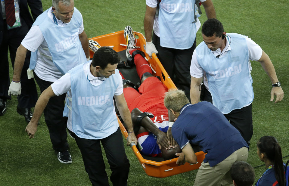 Photo - United States' Jozy Altidore is attended to by head coach Juergen Klinsmann, bottom, as he is carried off the pitch during the group G World Cup soccer match between Ghana and the United States at the Arena das Dunas in Natal, Brazil, Monday, June 16, 2014. (AP Photo/Hassan Ammar)