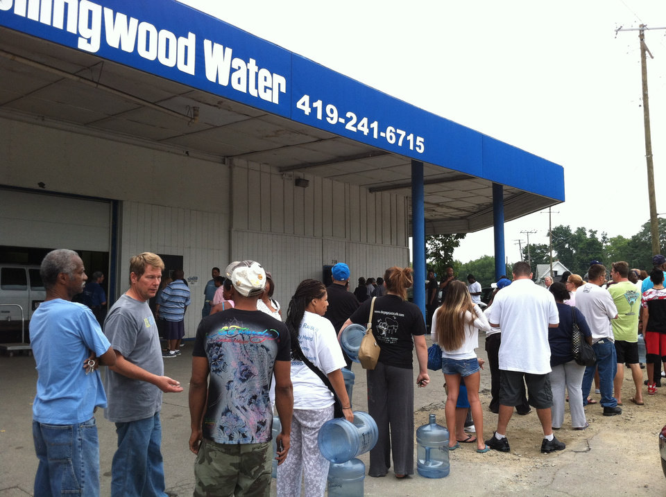 Photo - Residents in Toledo line up for water on Saturday, Aug. 2, 2014, in Toledo, Ohio. Ohio's governor is declaring a state of emergency in northwest Ohio, where about 400,000 people are being warned not to drink the water. Officials issued the warning Saturday after tests revealed the presence of a toxin possibly from algae on Lake Erie. (AP Photo/The Blade, Jetta Fraser) MANDATORY CREDIT; MAGS OUT; NO SALES; TV OUT; SENTINEL-TRIBUNE OUT; MONROE EVENING NEWS OUT; TOLEDO FREE PRESS OUT