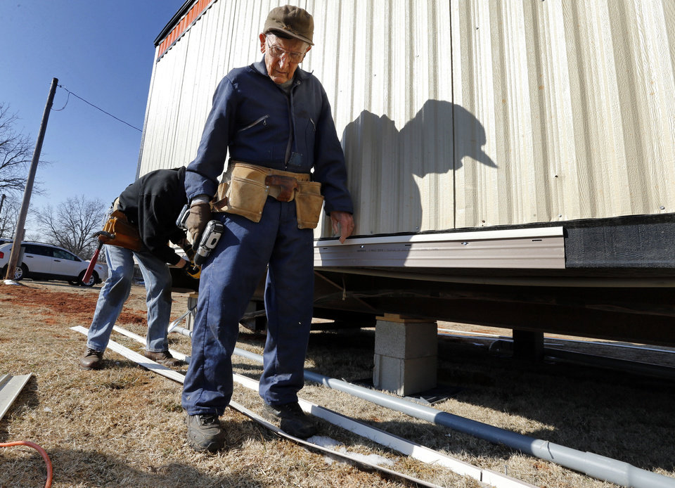 Photo -  Gerald Vincent, 87, installs skirting on a mobile home in Little Axe. He is a member of the  Nail Benders, an Oklahoma Baptist Disaster Relief team from First Baptist Church of Duncan.   STEVE SISNEY - THE OKLAHOMAN