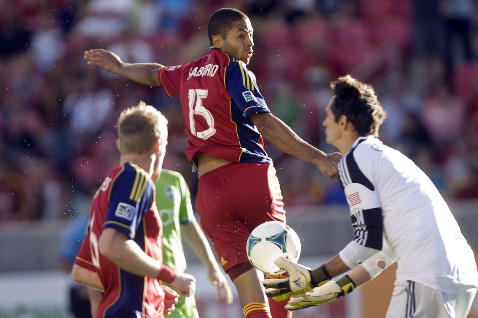 Photo - Real Salt Lake forward Alvaro Saborio (15) heads the ball and Seattle Sounders FC goalkeeper Michael Gspurning, right, makes a save during the first half of an MLS soccer game at Rio Tinto Stadium in Sandy, Utah, on Saturday, June 22, 2013. (AP Photo/The Salt Lake Tribune, Kim Raff) DESERET NEWS OUT; LOCAL TV OUT; MAGS OUT.