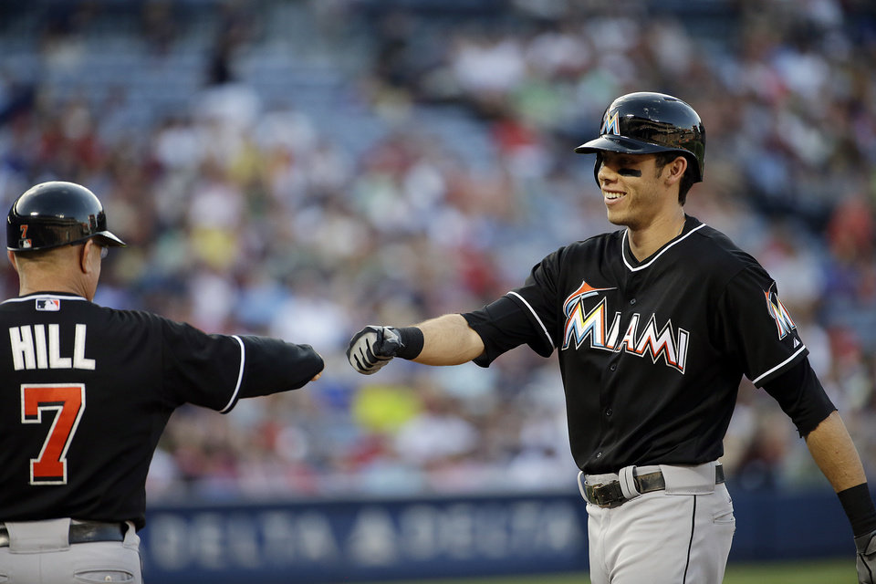 Photo - Miami Marlins' Christian Yelich, right, fist-bumps first base coach Perry Hill after hitting a single in the sixth inning of a baseball game against the Atlanta Braves, Sunday, Aug. 31, 2014, in Atlanta. (AP Photo/David Goldman)