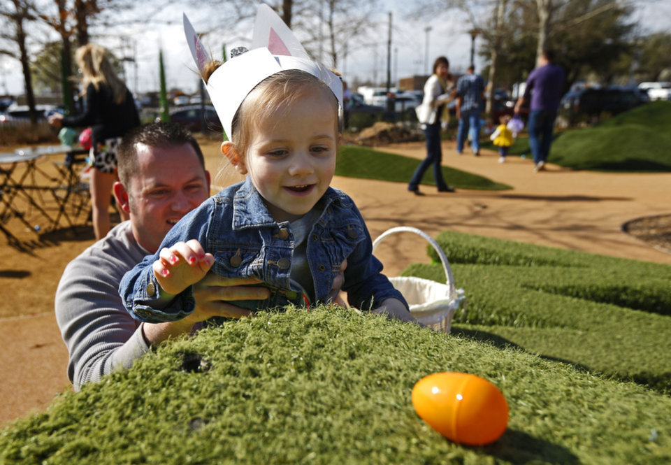 Chesney McLean, 3, of Oklahoma City, gets help from her dad, Aaron McLean, as she grabs an egg during an egg hunt at the Myriad Gardens in downtown Oklahoma City, Saturday, March 30, 2013. Photo by Bryan Terry, The Oklahoman