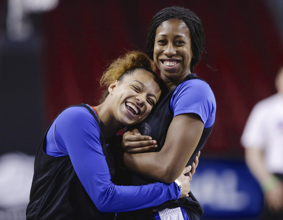 Photo - DePaul's Brittany Hrynko, left, and Jasmine Penny react after realizing their hug was being photographed during NCAA college basketball practice in Lincoln, Neb., Friday, March 28, 2014. DePaul will play Texas A&M in an NCAA Lincoln Regional women's semifinal basketball game on Saturday. (AP Photo/Nati Harnik)