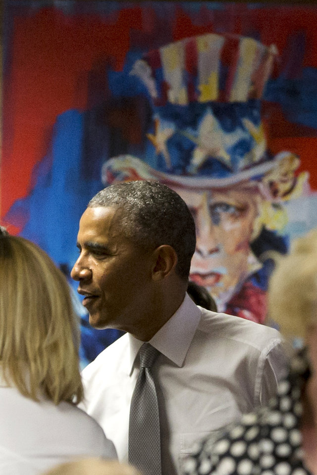 Photo - President Barack Obama stands by a painting of