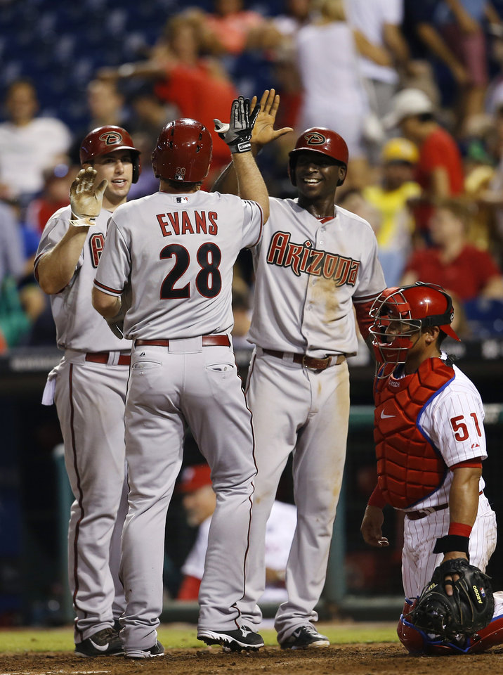 Photo - Arizona Diamondbacks' Nick Evans (28) celebrates with teammates Paul Goldschmidt, left, and Didi Gregorius, second from right, past Philadelphia Phillies catcher Carlos Ruiz, right, after hitting a three-run home run off relief pitcher Antonio Bastardo during the 10th inning of a baseball game, Saturday, July 26, 2014, in Philadelphia. Arizona won 10-6 in 10 innings. (AP Photo/Matt Slocum)