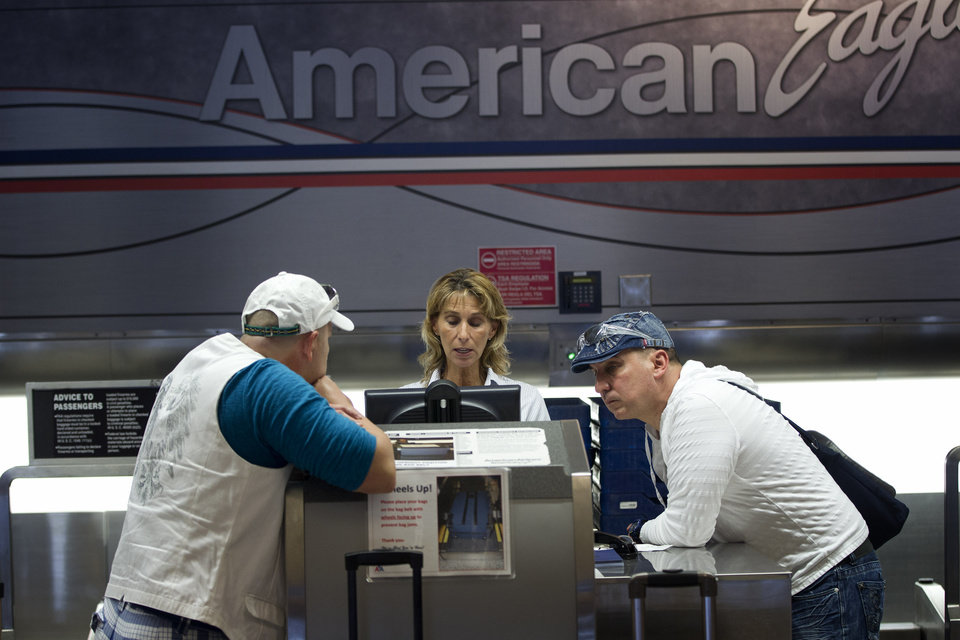 Two unidentified American Airlines passengers talk to a customer service representative, center, Friday, Oct. 5, 2012 in Miami, as they try to make arrangements for a flight, after their flight was cancelled. American Airlines says a combination of wear, poor design and even soda spilled into the tracks can cause seats on its Boeing 757s to pop loose during flight. American is canceling 44 flights today after it scrapped 50 flights Thursday because of the seat problem. The airline said Friday that all seat repairs on its Boeing 757 airplanes should be done by Saturday. (AP Photo/J Pat Carter)