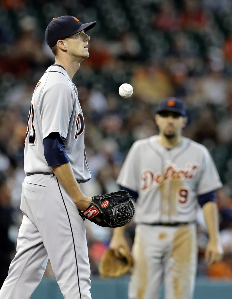 Photo - Detroit Tigers starting pitcher Drew Smyly, left, tosses the ball up as he waits for manager Brad Ausmus to pull him from the baseball game after giving up an RBI double to Houston Astros' L.J. Hoes in the third inning, Sunday, June 29, 2014, in Houston. Nick Castellanos (9) stands in the background. (AP Photo/Pat Sullivan)