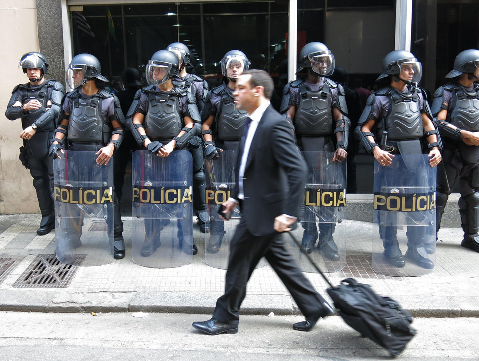Photo - A pedestrian walks by a line of police officers as they block the entrance of the Transportation Department when subway workers arrive to request a meeting with officials, to negotiate better salaries and benefits in Sao Paulo, Brazil, Monday, June 9, 2014. Striking subway workers clashed in a central commuter station Monday while union leaders threatened to maintain the work stoppage through the World Cup's opening match in Sao Paulo this week. (AP Photo/Adriana Gomez Licon)