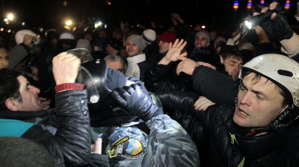 Photo - Pro-European Union activists try to remove a helmet from a riot police officer near a Svyatoshin police station in Kiev, Ukraine, Saturday, Jan. 11, 2014. Kiev has been the scene of massive pro-European protests for more than a month, triggered by Ukrainian President Viktor Yanukovych's decision to ditch a key deal with the European Union in favor of building stronger ties with Russia. (AP Photo/Sergei Chuzavkov)