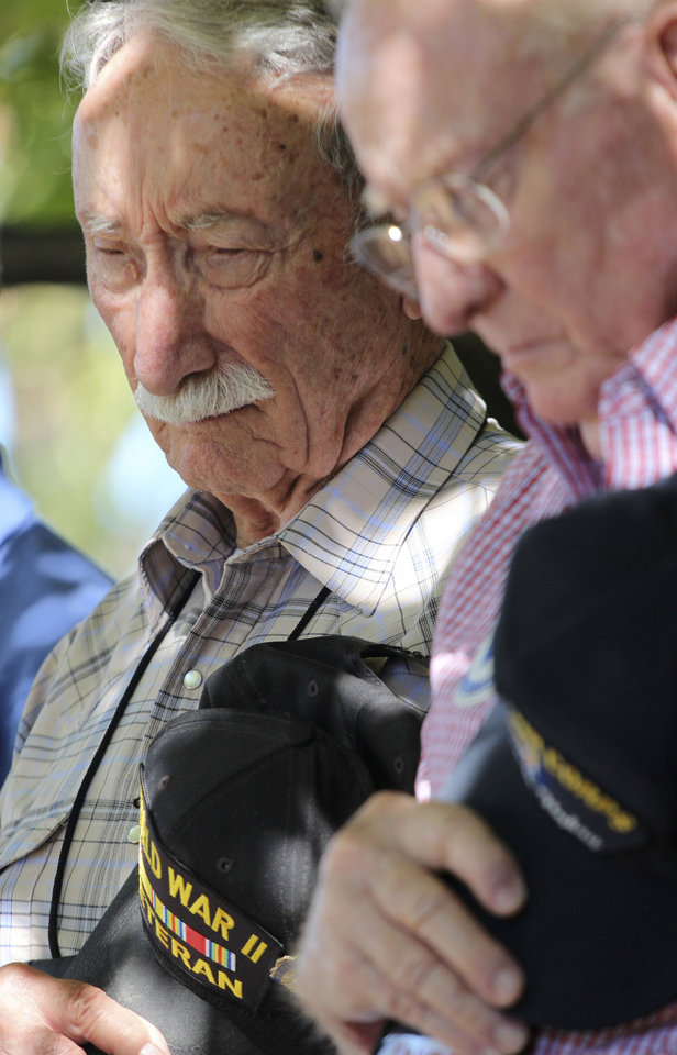 Photo - In this Sept. 27, 2013 photo, George Williams, left, and Robert Crouse, bow their heads as they take part in a memorial ceremony during a reunion outside the U.S. Air Force Museum at Wright Patterson Air Force base in Dayton, Ohio. As many as 11,000 people, including Williams and Crouse, served in the 57th Bomb Wing that flew missions over German-held Europe from North Africa and the island of Corsica during most of the war. Hundreds survive, according to wing historians and reunion organizers. Only nine veterans made it to this fall's event. (AP Photo/Tom Uhlman)