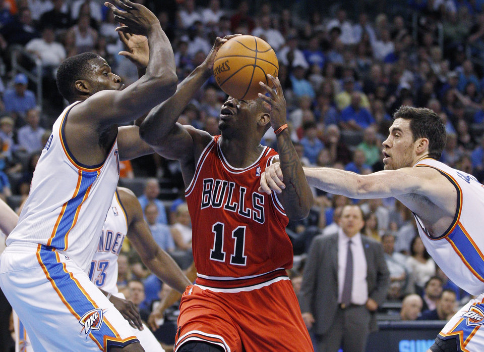 Photo -   Oklahoma City Thunder center Nick Collison, right, reaches in and fouls Chicago Bulls guard Ronnie Brewer (11) as he drives between Collison and center Nazr Mohammed, left, in the second quarter of an NBA basketball game in Oklahoma City, Sunday, April 1, 2012. (AP Photo/Sue Ogrocki)