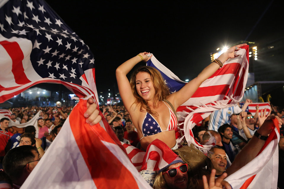 Photo - Fans of the U.S. national soccer team celebrate their team's victory during a live broadcast of the soccer World Cup match between the Unites States and Ghana, inside the FIFA Fan Fest area on Copacabana beach, Rio de Janeiro, Brazil, Monday, June 16, 2014. Clint Dempsey scored in the first minute and rookie substitute John Brooks scored a late game winner as the U.S. defeated Ghana 2-1 in the World Cup opener for both. (AP Photo/Leo Correa)