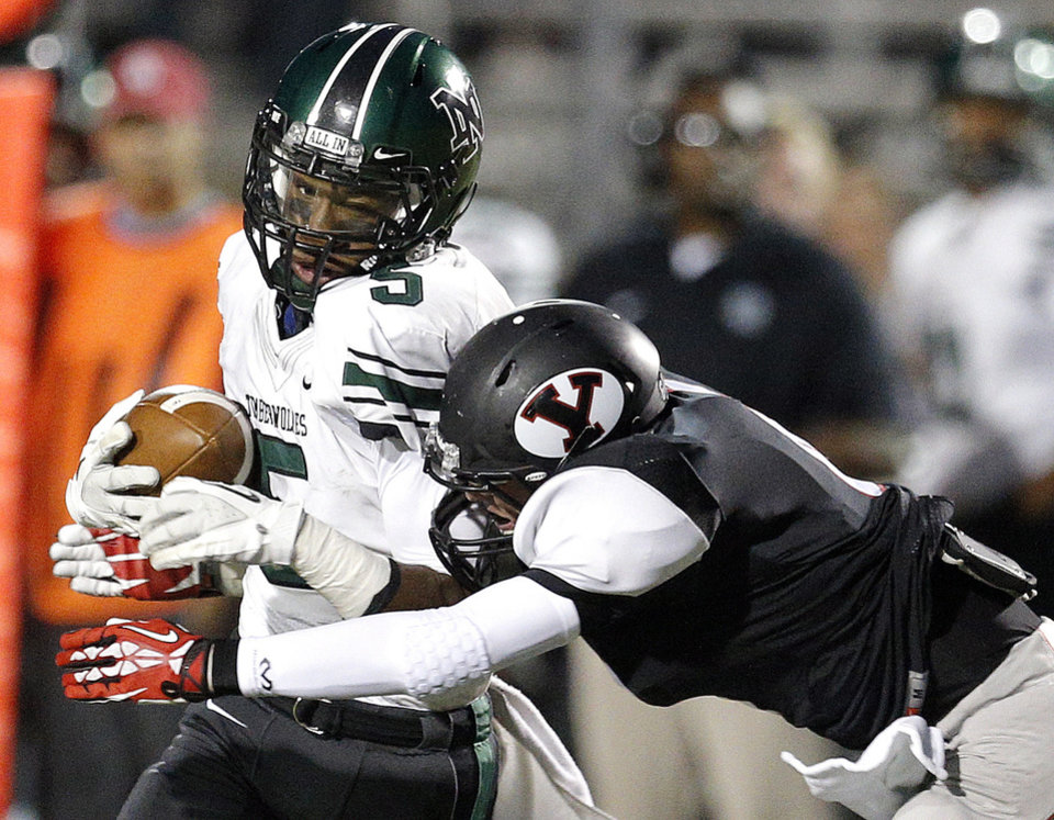 Norman North's Nick Basquine is tackled by Yukon's Nick Bryant during a high school football game between Yukon and Norman North in Yukon, Okla.,   Friday, Oct. 4, 2013. Photo by Sarah Phipps, The Oklahoman